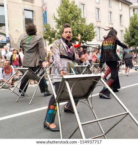 AURILLAC, FRANCE - AUGUST 23:  dancer carrying a bar stool in the middle of the crowd as part of the Aurillac International Street Theater Festival, Cie Oposito,on august 23, 2013, in Aurillac,France  - stock photo