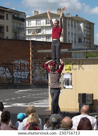 AURILLAC, FRANCE, AUGUST 21: Female acrobat standing on the shoulders of his partner in the street as part of the Aurillac international Street Theater Festival, on august 21, 2014 in Aurillac,France. - stock photo