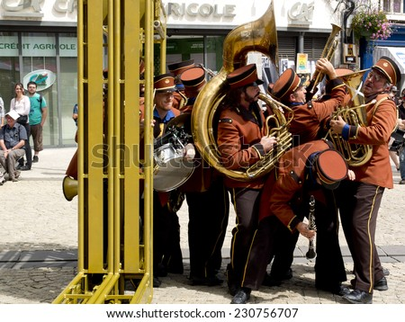 AURILLAC, FRANCE, AUGUST 22: Funny musicians of a fanfare wearing orange uniforms as part of the Aurillac international Street Theater Festival, on august 22, 2014 in Aurillac, France. - stock photo