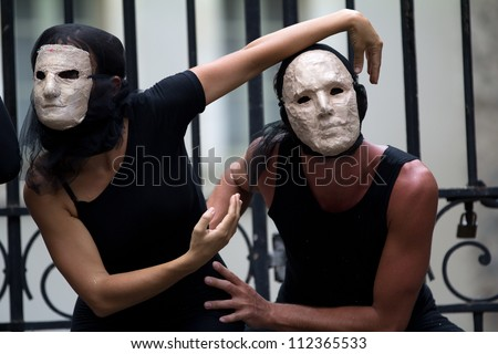 AURILLAC, FRANCE - AUGUST 23: mysterious actors wearing a white mask as part of the Aurillac International Street Theater Festival, show La diagonale du Fou, on august 23, 2012, in Aurillac,France. - stock photo