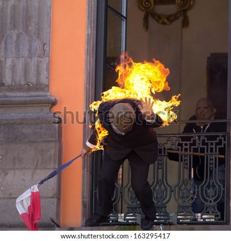 AURILLAC, FRANCE - AUGUST 21: Portrait of an actor wearing clothes on fire as part of the Aurillac International Street Theater Festival, Spectacle d'Ouverture,on august 21, 2013, in Aurillac,France  - stock photo