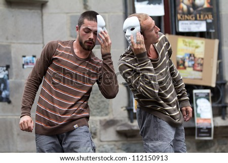AURILLAC, FRANCE - AUGUST 24: two masked dancers, side to side, as part of the Aurillac International Street Theater Festival,show by the Company Idem,on august 24, 2012, in Aurillac,France. - stock photo