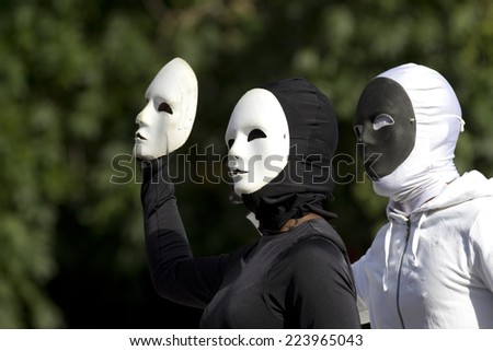 AURILLAC, FRANCE-AUGUST 25: two masked people play with their black and white masks as part of the Aurillac International Street Theater Festival, cie Bakhus 24,on august 25,2014, in Aurillac,France.  - stock photo