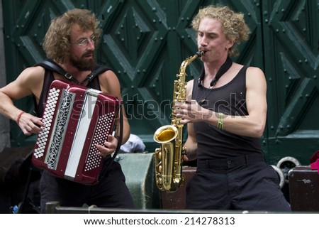 AURILLAC, FRANCE- AUGUST 20: two musicians,an accordionist and a saxophonist, play in the street as part of the Aurillac International Street Theater Festival, on august 20, 2014, in Aurillac,France.  - stock photo