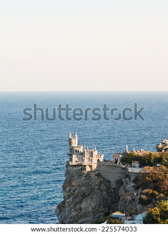 Aurora cliff with Swallow's Nest castle on Southern Coast of Crimea in evening - stock photo