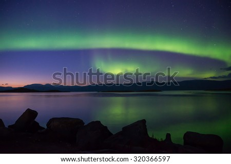 Aurora lights dancing over calm lake in Abisko (Aurora borealis) - stock photo