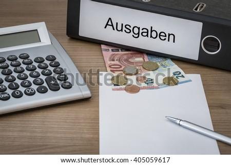 Ausgaben (German Expenses) written on a binder on a desk with euro money calculator blank sheet and pen - stock photo