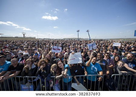 AUSTIN, TEXAS - FEBRUARY 27, 2016: An excited crowd of Bernie Sanders supporters wave signs while awaiting the candidate's arrival for a campaign rally at the Circuit of the Americas. - stock photo