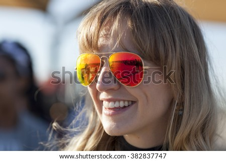 AUSTIN, TEXAS - FEBRUARY 27, 2016: The line waiting to enter the Circuit of the Americas for a Bernie Sanders campaign rally is reflected in the sunglasses of Lauren Hartnett. - stock photo