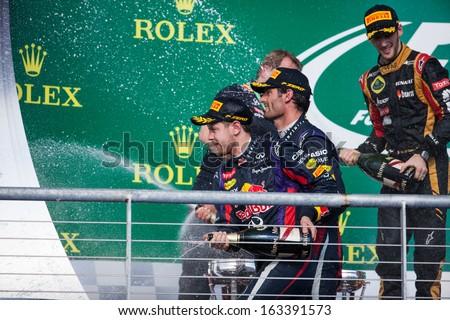 AUSTIN, TEXAS - NOVEMBER 17. Vettel, Webber, and Grosjean spray celebratory champaign on the podeum after the Formula 1 United States Grand Prix on November 17, 2013 in Austin, Texas.  - stock photo