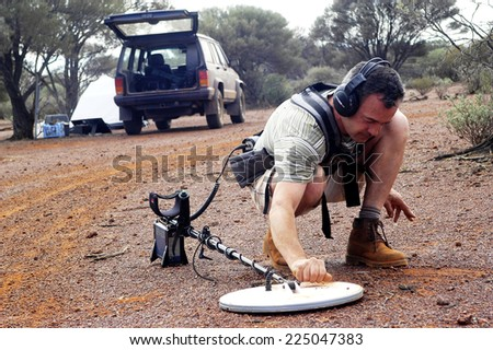 AUSTRALIA - MAY 13: The gold miner refine the search by passing the detection handful of soil growing small to find the golden nugget, may 13, 2007. - stock photo