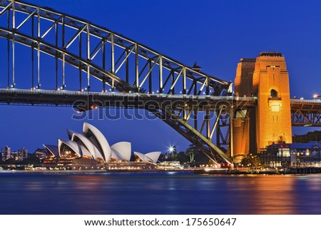 Australia NSW Sydney iconic landmarks illuminated harbour bridge at sunset with reflection in harbour waters close-up fragment - stock photo