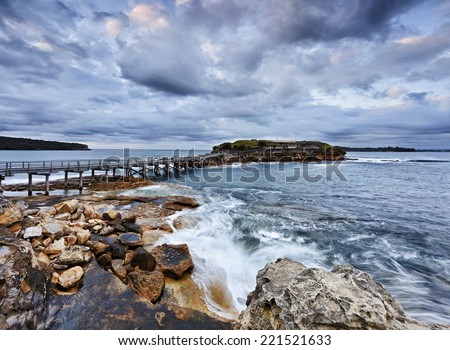 australia pacific coastline near Sydney entrance to Botany bay view on Bare island with navi citadel connected by historic wooden bridge at sunrise - stock photo
