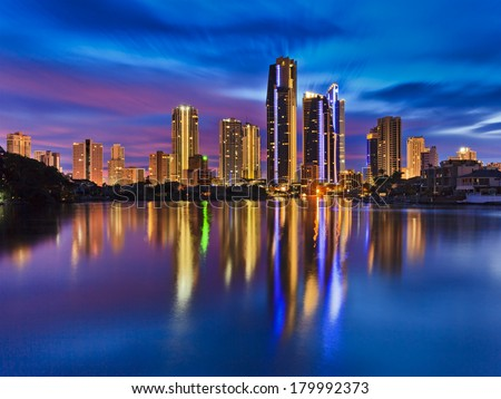Australia QUeensland SUrfers paradise CBD city reflection in still waters of river at sunrise blue-pink cloudy sky  - stock photo