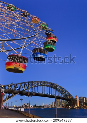 Australia sydney CBD and harbour bridge landmarks view from underneath ferry-wheel with colorful cabins in the sky above the bridge arch - stock photo