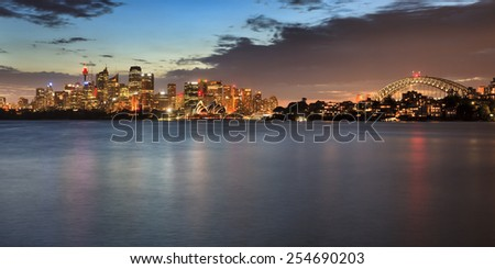 Australia Sydney CBD distant view from Cremorne point across the harbour with skyscraper towers and Arch of the bridge in panoramic view at sunset - stock photo