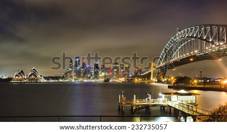 AUstralia Sydney CBD landmarks city skyscrapers and harbour bridge arch after sunset brightly illuminated from dwarf to circular quay - stock photo