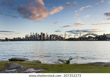 Australia Sydney CBD view over harbour waters at sunset with green grass in foreground and panoramic view to city and harbor bridge - stock photo