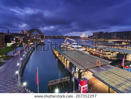 Australia Sydney circular quay waterfront piers at sunset with view towards harbour bridge, museum, passenger terminal and other landmarks - stock photo