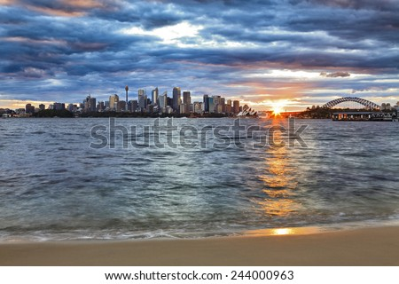 Australia Sydney city CBD and Harbour bridge landmarks at sunset with sun touching horizon and blurred harbour waves on sandy beach  - stock photo