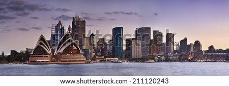 australia sydney city CBD panoramic view from Kirribilli over harbour at sunset with illuminated high-rise buildings landmarks - stock photo