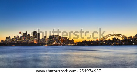 australia Sydney city CBD panoramic view with Harbour bridge at sunset with illuminated skyscrapers and blurred water - stock photo