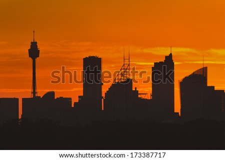 Australia Sydney city CBD silhouette distant view at sunset high contrast against bright orange sky - skyscrapers and towers - stock photo
