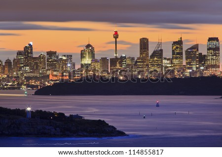 Australia Sydney City CBD view from north head entrance to Sydney harbour at sunset with illuminated lights and blurred water - stock photo