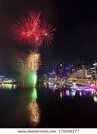 Australia Sydney Darling Harbour water reflects fireworks and city CBD lights during festive season - stock photo