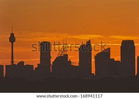 Australia Sydney distant CBD silhouette of skyscrapers and towers at sunset against the sun summer time heat in the city - stock photo