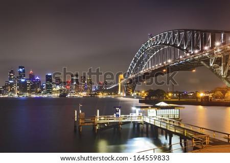 australia sydney landmarks sunset view over harbour bright illuminated buildings of city CBD and arch of harbour bridge - stock photo
