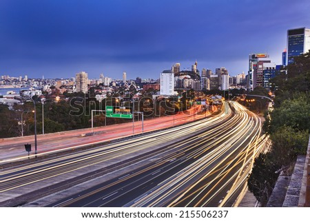 australia SYdney motorway with heavy traffic at rush hour view towards city CBD landmarks at sunset with blurred vehicle lights - stock photo