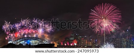 Australia SYdney New Year fireworks distant panoramic view of light show over city CBD and harbour bridge at midnight - stock photo