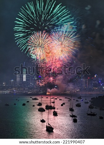 Australia SYdney New Year fireworks green color light balls over city CBD skyscrapers reflecting in harbour water - stock photo