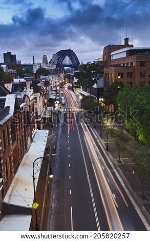 Australia Sydney The Rocks streets and rooftops from bridge at sunset blurred motor traffic with city lights and illumination - stock photo