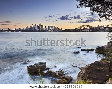 Australia SYndye city CBD view from Cremorne at sunset with blurred harbour waters and rocks at low tide - stock photo