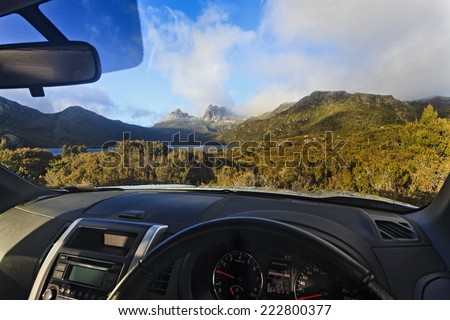 australia tasmania cradle mountain national park lake dove car park and 4wd rented vehicle looking at landmarks sunny morning through the windscreen - stock photo