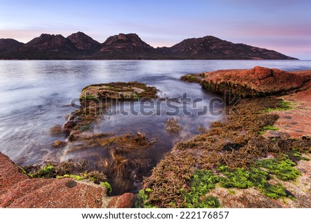 Australia Tasmania Freycinet national park coles bay at sunrise with red granite coastline and Hazards mountains in the background illuminated by rising warm sun light - stock photo