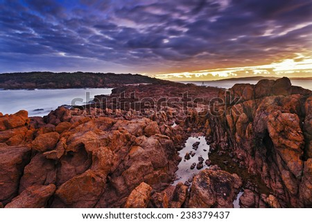 australia tomaree national park big rocky sea shore at sunset blurred stormy clouds and red rocks formation at low tide - stock photo