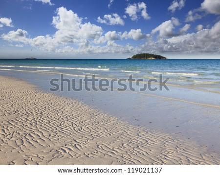 australia whitsunday island national park white sand beach with waves and islands on horizon under blue sky - stock photo