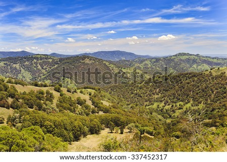 australian barrington tops mountains in national park on a sunny summer day viewed from remote lookout towards green hils and ranges - stock photo