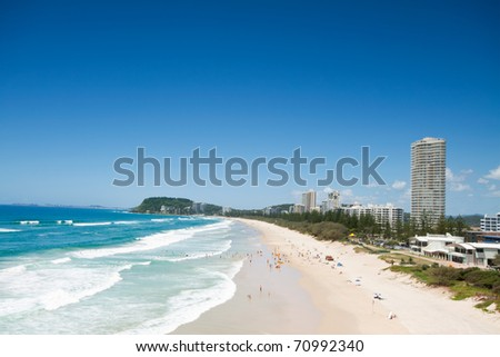 australian beach during the day with buildings beside (burleigh heads,qld) - stock photo