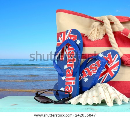 Australian beach scene with Aussie sandals, beach bag, sunglasses and shell with view of blue ocean. - stock photo