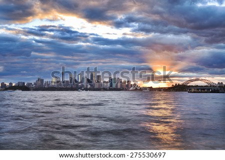 Australian landmarks of Sydney - cityscape, harbour and bridge at sunset with setting sun touching horizon behind skyscrapers - stock photo
