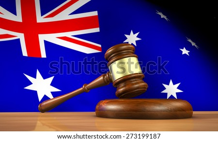 Australian law and justice concept with a 3d rendering of a gavel on a wooden desktop and the flag of Australia on background. - stock photo