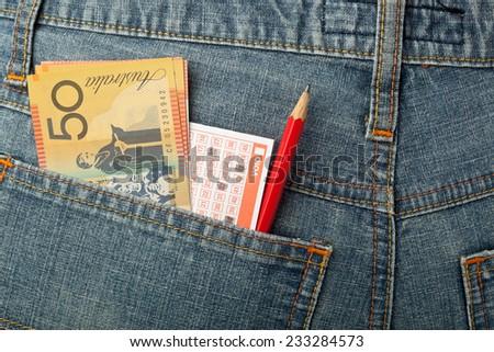 Australian money and lottery bet slip in back pocket  - stock photo