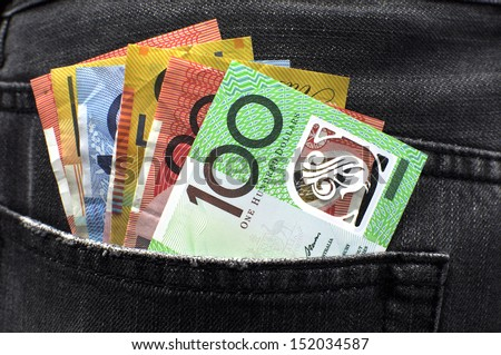 Australian money including 100, 50, 5, 10 and 20 dollar notes, in back pocket of a man's black charcoal jeans pocket. - stock photo