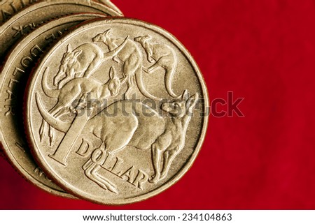 Australian money.  One dollar coins over red background.  Overhead view. - stock photo