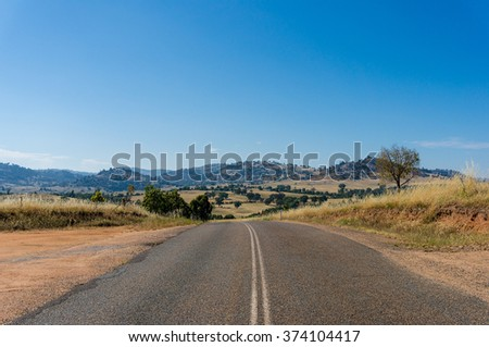 Australian outback road. Rural road on sunny day. Young region, NSW, Australia - stock photo