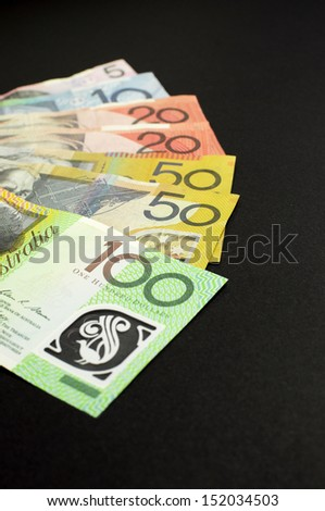 Australian paper money, including one hundred, twenty, ten, five and fifty dollar notes against a black background. Vertical with copy space. - stock photo